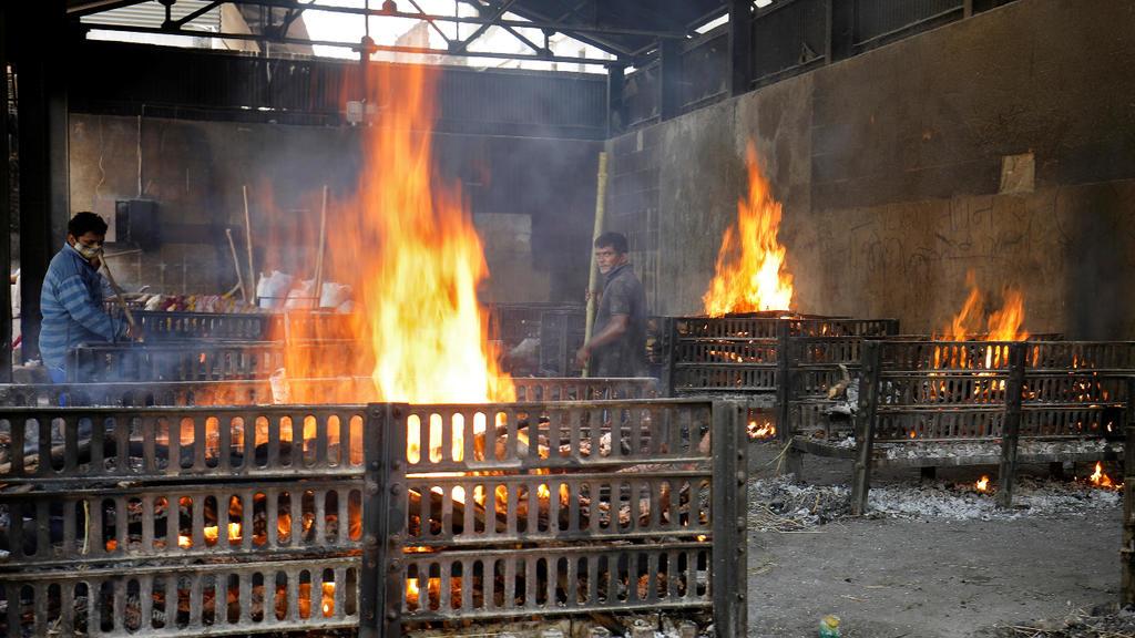 Un grupo de personas encienden piras funerarias para cremar los cuerpos de quienes fallecieron por Covid-19 en la ciudad de Ahmedabad, India,